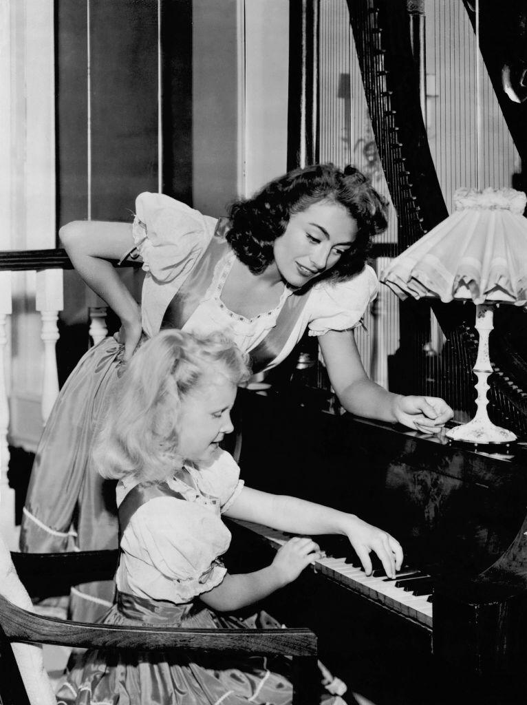 Joan Crawford helping her daughter Christina during her piano lesson in the United States on July 25, 1947 | Photo: Getty Images