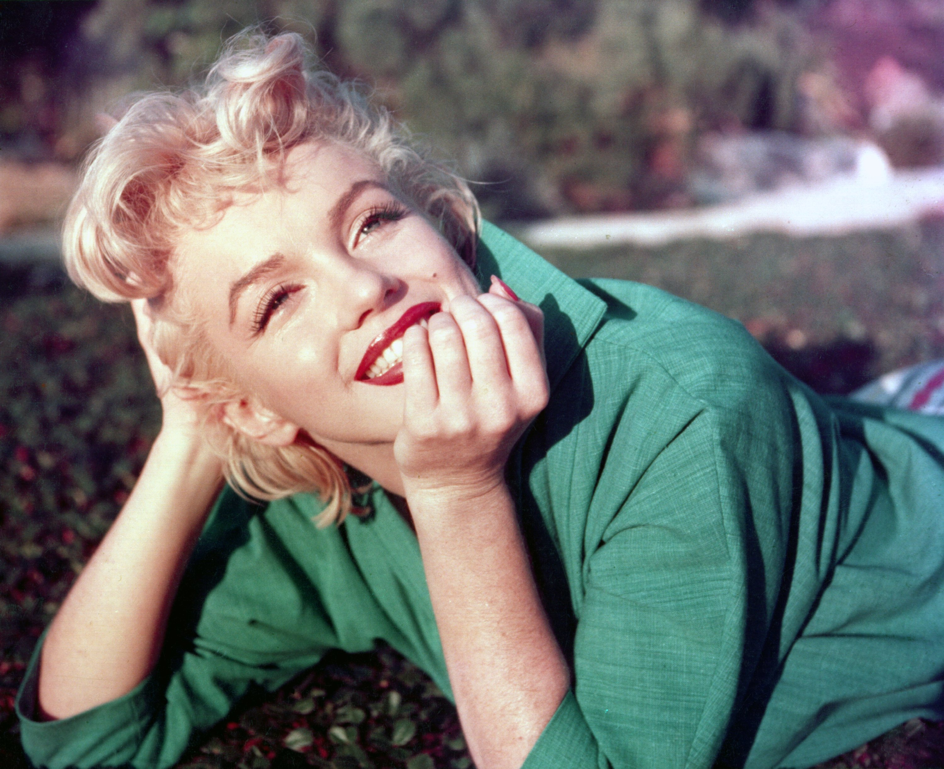 Actress Marilyn Monroe poses for a portrait laying on the grass in 1954 in Palm Springs, California. | Source: Getty Images