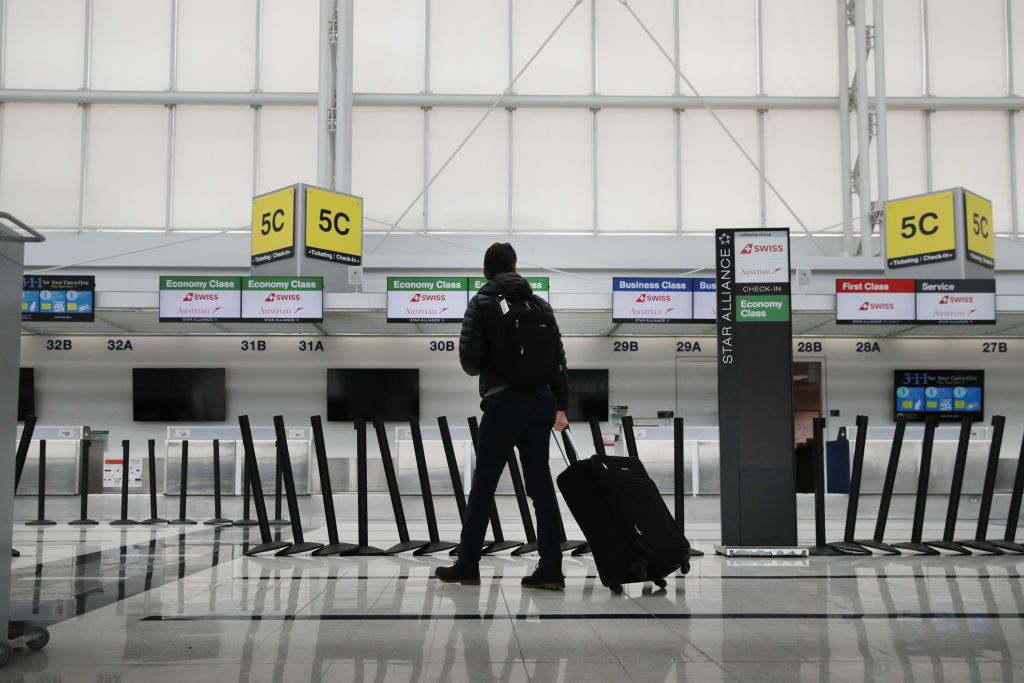 A person walking in the airport with a luggage.   Source: Shutterstock