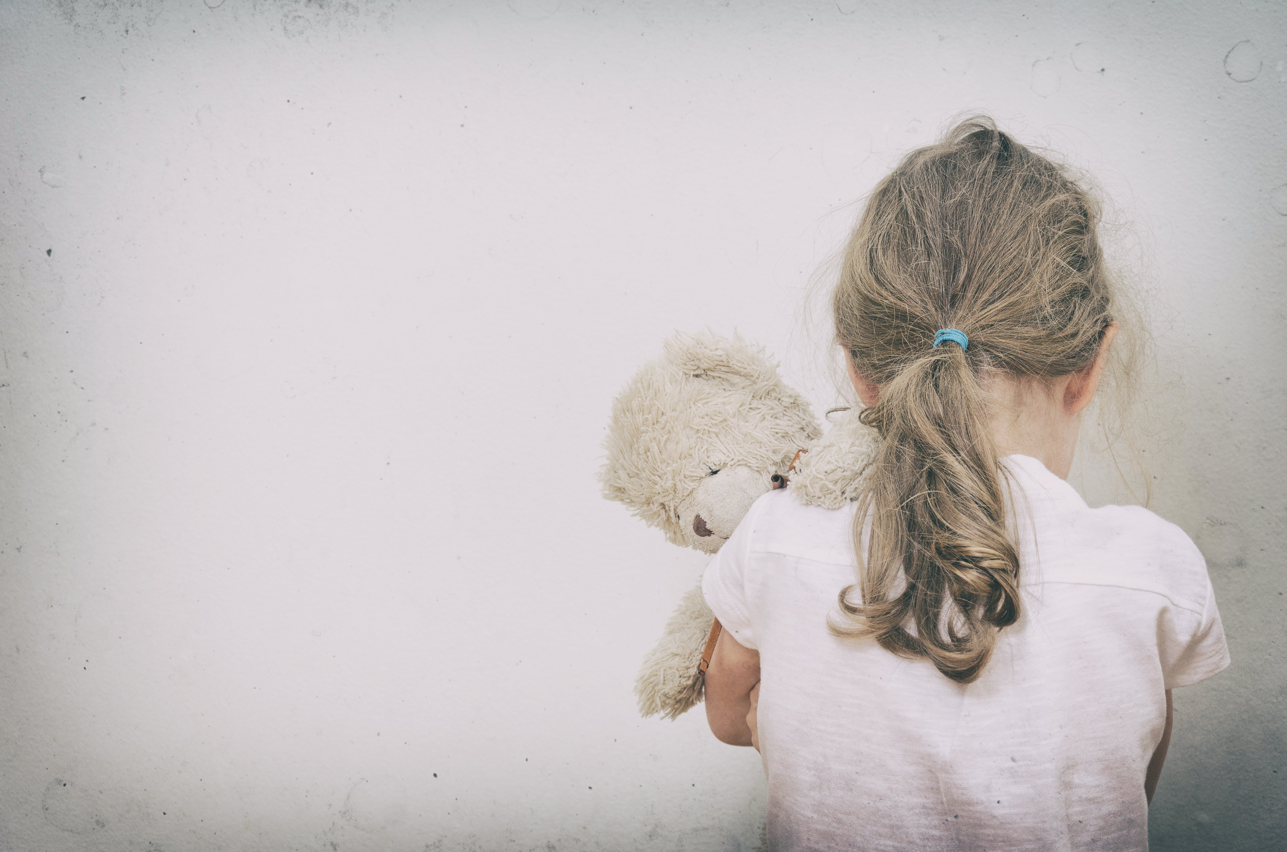 A sad little girl from the back holding her teddy bear.   Source: Shutterstock