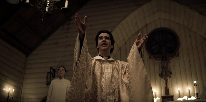 """Father Paul (Hamish Linklater) preaches to his people as acolyte Bev Keane (Samantha Sloyan) looks on in """"Midnight Mass."""""""