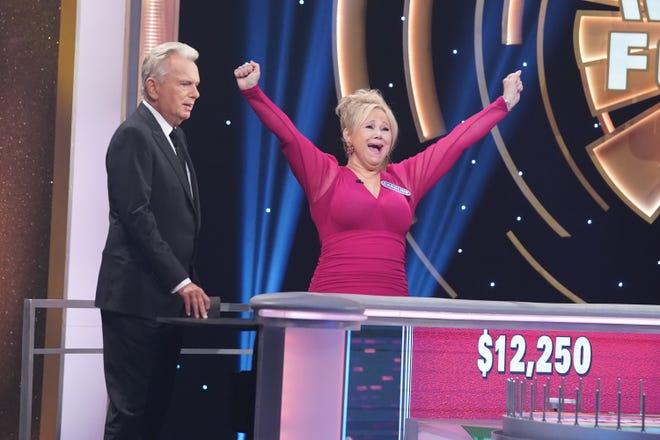 """Celebrity Wheel of Fortune"" host Pat Sajak, left, looks on as contestant Caroline Rhea celebrates on the Oct. 3 episode."