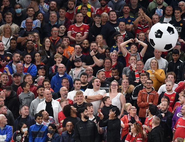 Supporters play with an inflatable ball during the English League Cup third round football match between Manchester United and West Ham United at Old Trafford