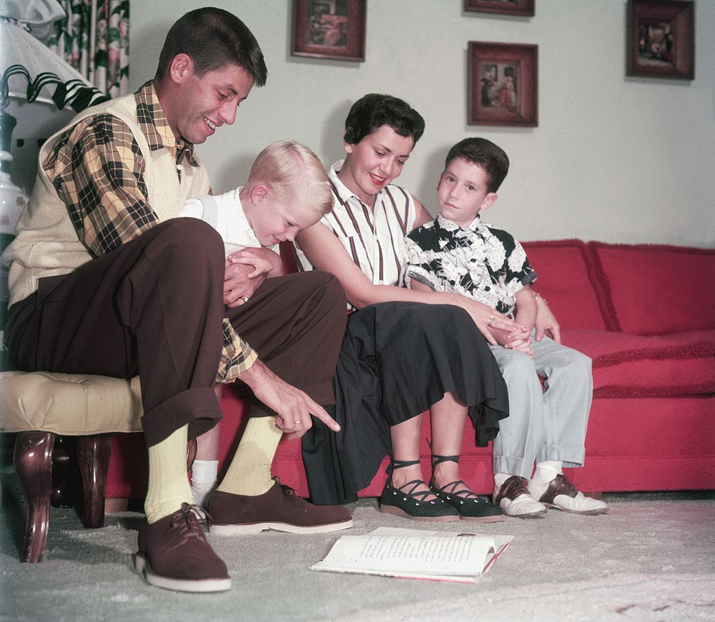 American actor and comedian Jerry Lewis sitting on a couch with wife, Patti Palmer, and their two sons, Gary and Ronald circa 1960 |