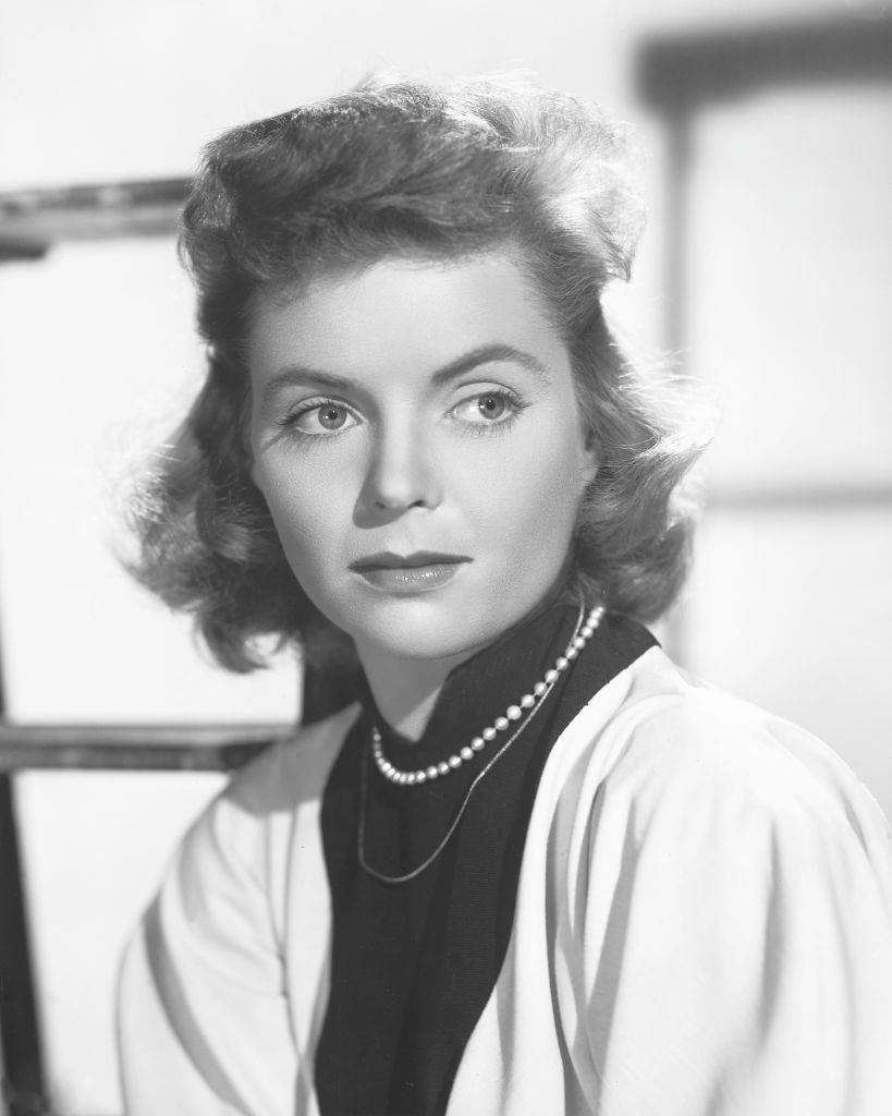Dorothy McGuire (1916-2001) wearing a white cardigan over a black high-neck blouse with a pearl necklace, in a studio portrait, circa 1950. |