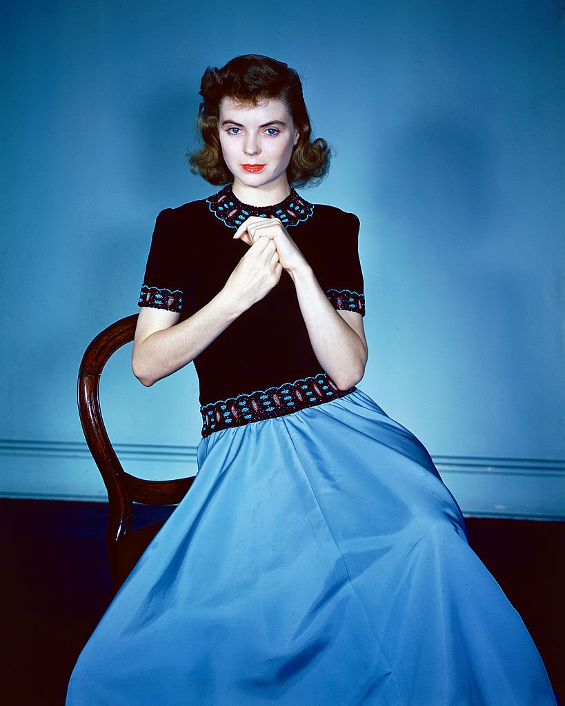 Dorothy McGuire (1916-2001) sitting on a chair, wearing a black top with red and blue trim and a blue skirt in a studio portrait, circa 1940. |