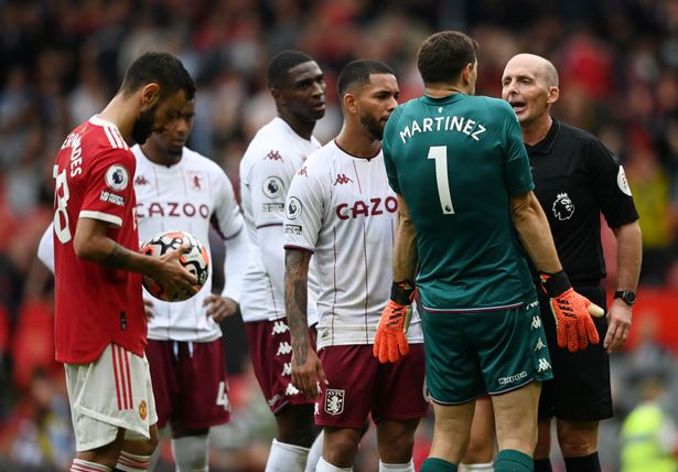 Referee Mike Dean speaks to Emiliano Martinez of Aston Villa during the Premier League match between Manchester United and Aston Villa at Old Trafford on September 25, 2021 in Manchester, England.