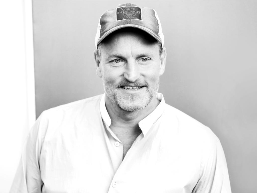 Imagen en blanco y negro de Woody Harrelson con una gorra de béisbol con una camisa blanca