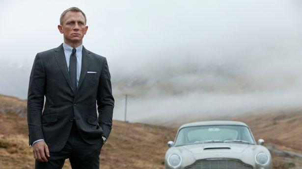 Daniel Craig stars as James Bond in Skyfall standing next to an Aston Martin car
