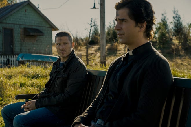 """Father Paul (Hamish Linklater, right) tries to reach out and bond with the returned Riley (Zach Gilford) in """"Midnight Mass."""""""